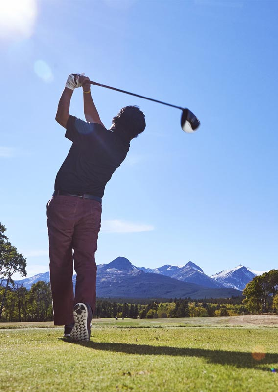Man swinging golf club at East Glacier