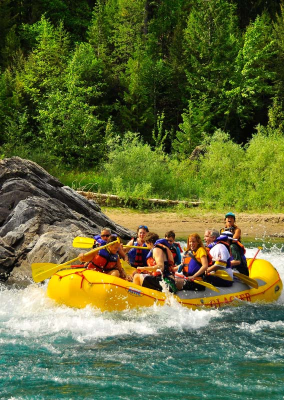 A group of rafters splash up near a big rock on a blue river.