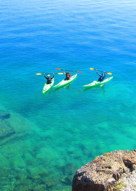 Three kayakers raise their paddles over their heads as they float on a clear blue lake.