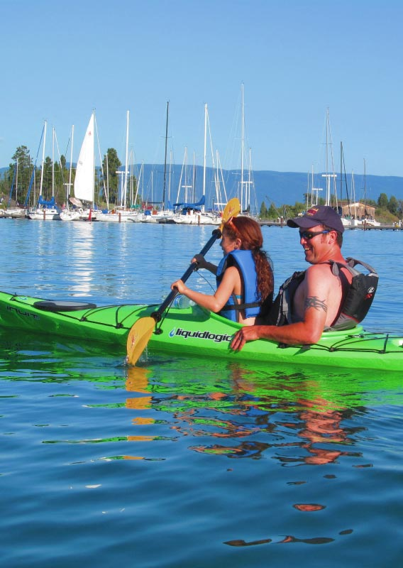 A man and a child sit in a kayak, paddling on a lake near a marina.