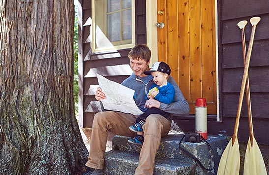 A dad and child sit on the steps of a wooden cabin.