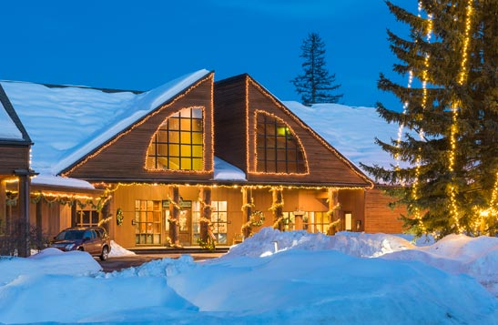 A lodge with large windows covered with snow and Christmas lights.