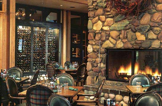 A rustic dining room with a large stone fireplace.