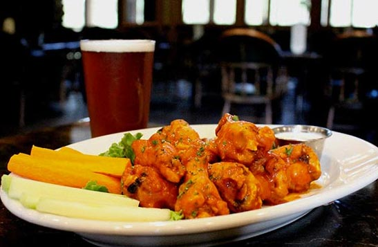 A plate of saucy chicken wings and a pint of beer.
