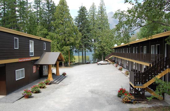 Motel Lake McDonald nestled between tall coniferous and deciduous trees.