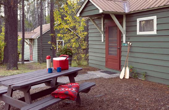 A green cabin and picnic table with camping gear on it.
