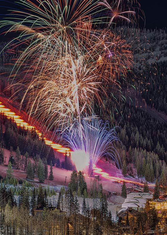 Fireworks shooting into the sky from a ski hill