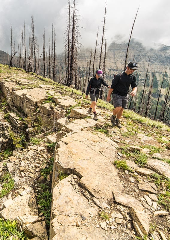 Two hikers walk along a ridge with a dramatic cliff drop on one side of the path