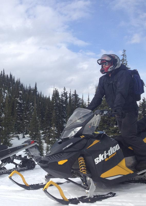Two snowmobilers standing and looking out with snow covered mountains