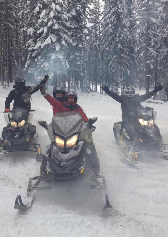 Three snowmobiles with excited sledders