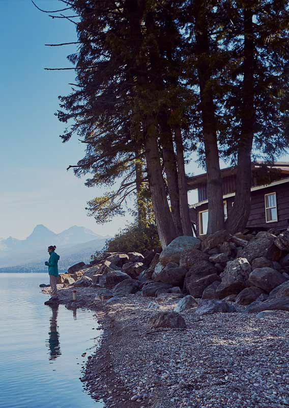 Woman stands on bank of calm Lake McDonald as a man in a canoe approaches
