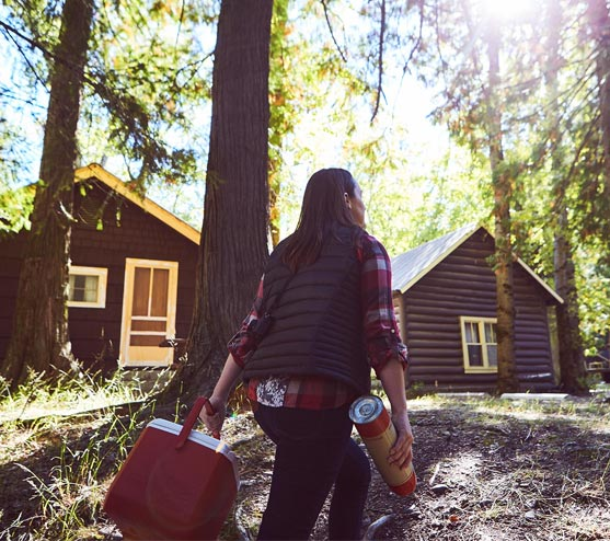 A person walks among trees towards wooden cabins with a cooler and hot drink thermos