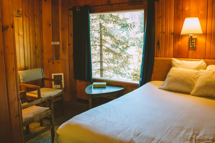 A bed sits next to a large window in a wooden cabin.