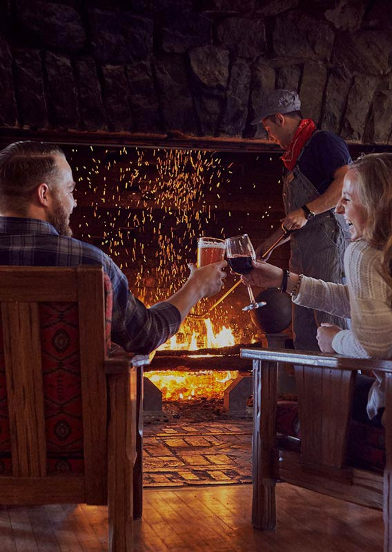 Glacier Park Lodge Lobby fireplace burns behind romantic cheers between couple