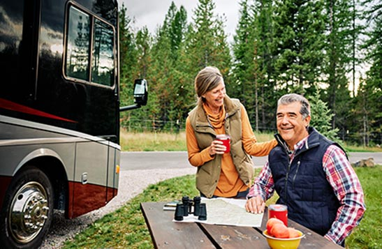 Couple enjoys coffee while reviewing a map of Glacier National Park at a picnic table