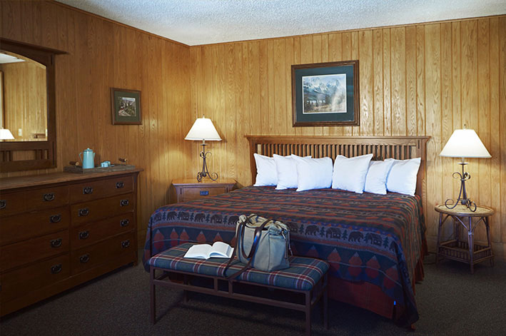 Bedroom with one king bed in a Glacier Park Lodge suite