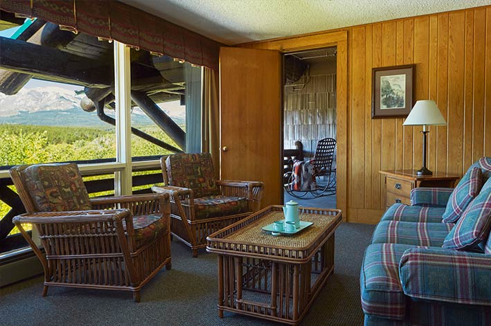 Spacious sitting area and adjacent private balcony in a suite in Glacier Park Lodge