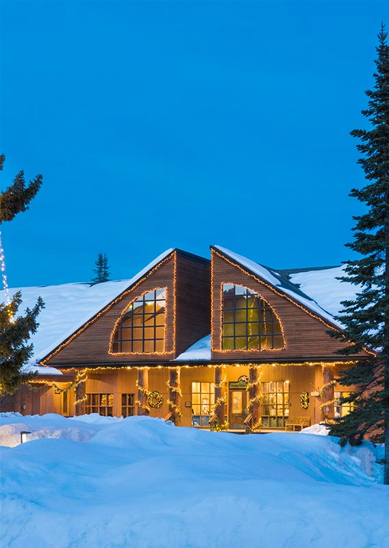 Grouse Mountain Lodge in the winter with Christmas lights adorning large windows and wooden columns