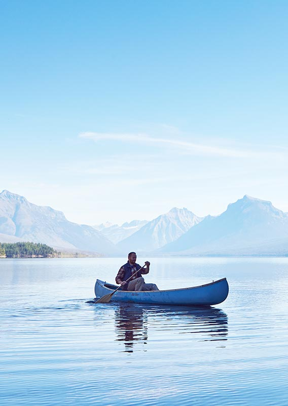 Man canoeing on a lake, woman on shore. Mountains across the lake.