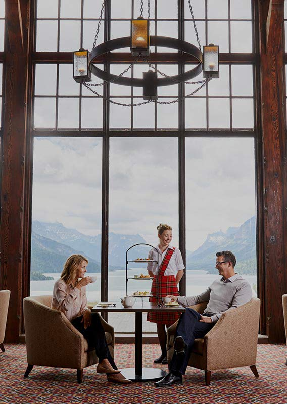 A couple sitting for Afternoon Tea overlooking Upper Waterton Lake
