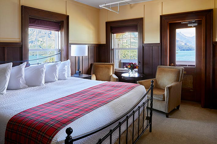 Well-appointed hotel room with one king bed, sitting area and views of Waterton Lake