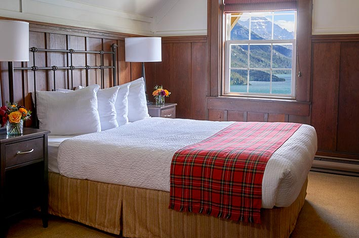 Well-appointed hotel room with one queen bed and views of Waterton Lake