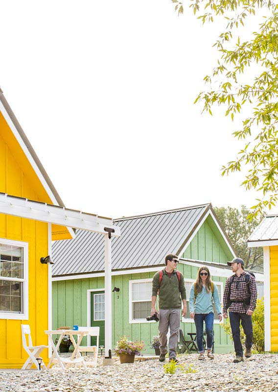 A group of people walk around colorful tiny homes