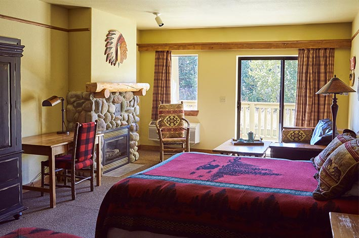 Great Bear Lodge Superior Room at St. Mary Village featuring a river rock fireplace and sitting area