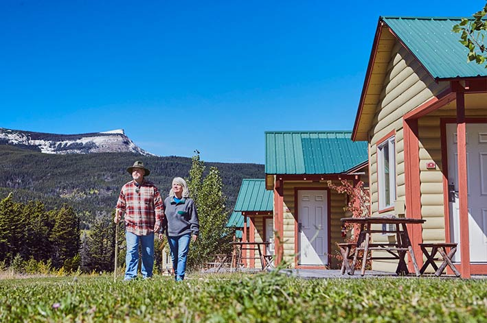 Couple walking in the grass outside the Glacier Cabins at St. Mary Village