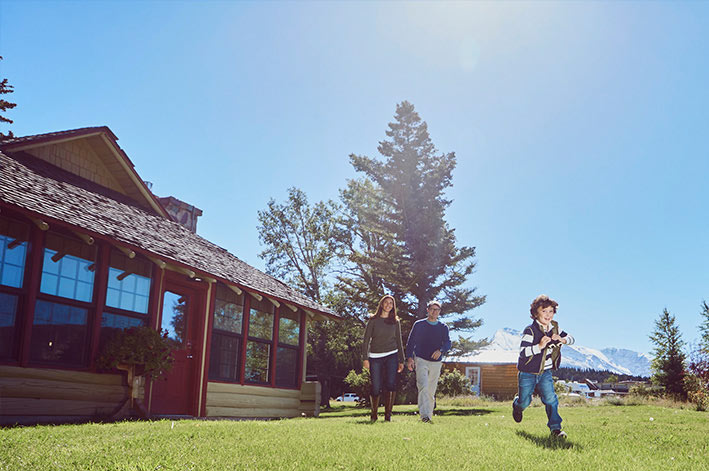 Parents and a young son walking on the grass in front of the Homestead House at st. Mary Village