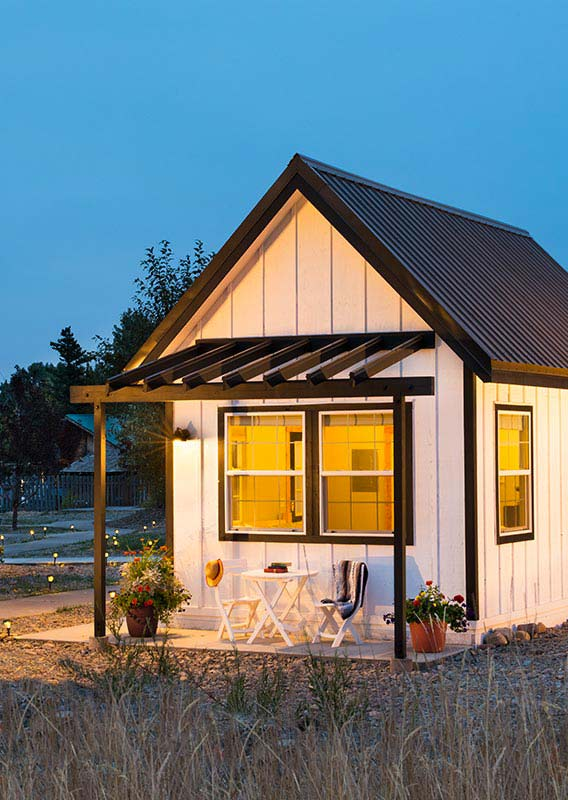 A white tiny home with an inviting porch at dusk