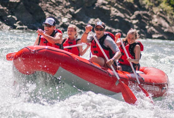Four people on a red raft paddle through rapid waters