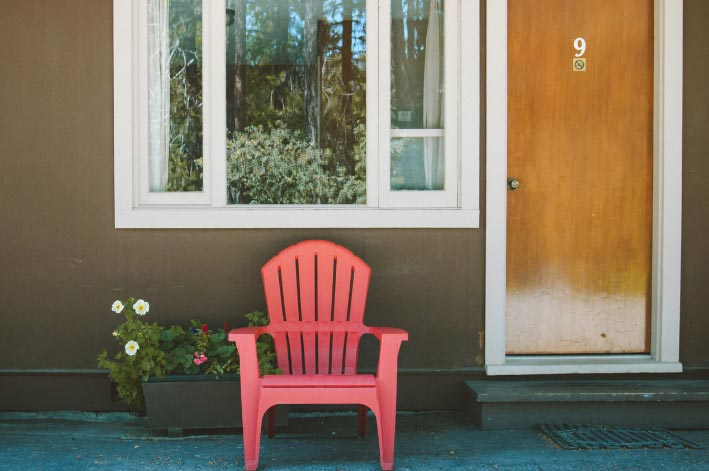 A red chair and flowerpots sits below a window next to a door.
