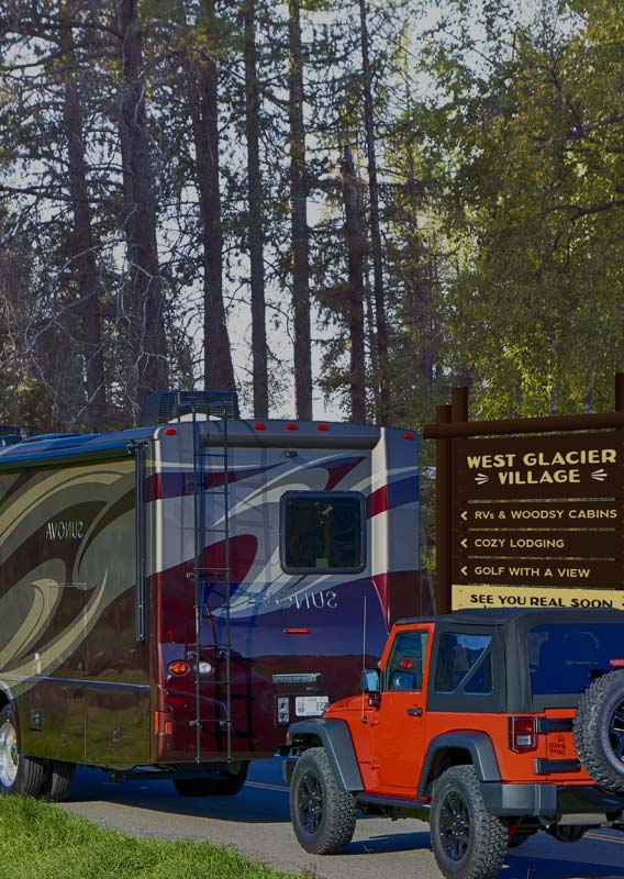 An RV drives past the entrance sign for the West Glacier RV park.