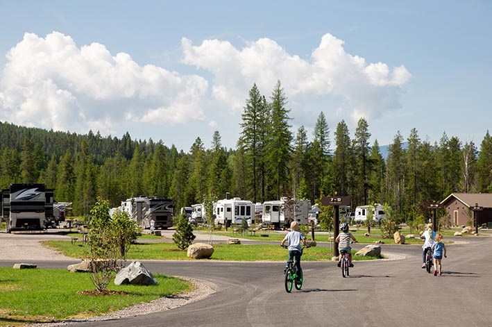 A group of kids bike along the quiet streets of the RV park in the summer time