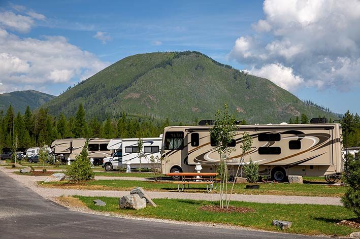 RVs parked in grassy RV park sites with mountain above them