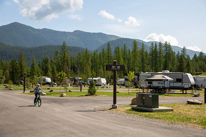 RV park road with signage and child biking through