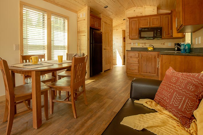 A table and couch inside a wooden cabin.