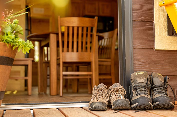 Two pairs of hiking boots on a wooden porch