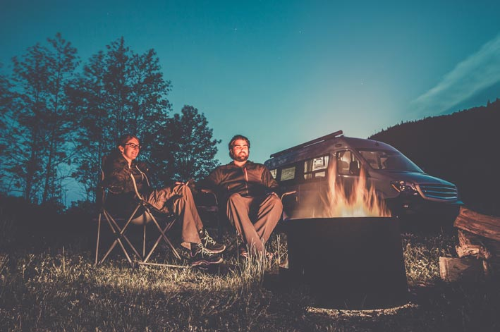 Two people sit around a campfire next to a camper fan.