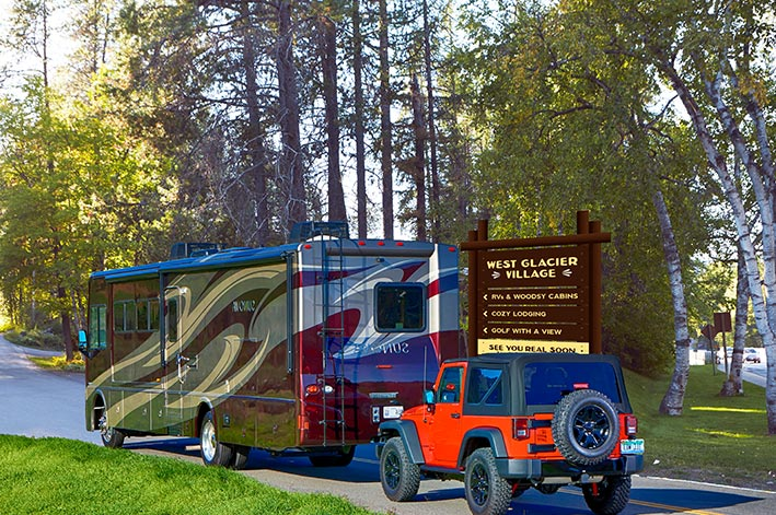 An RV pulling a Jeep enters an RV park.