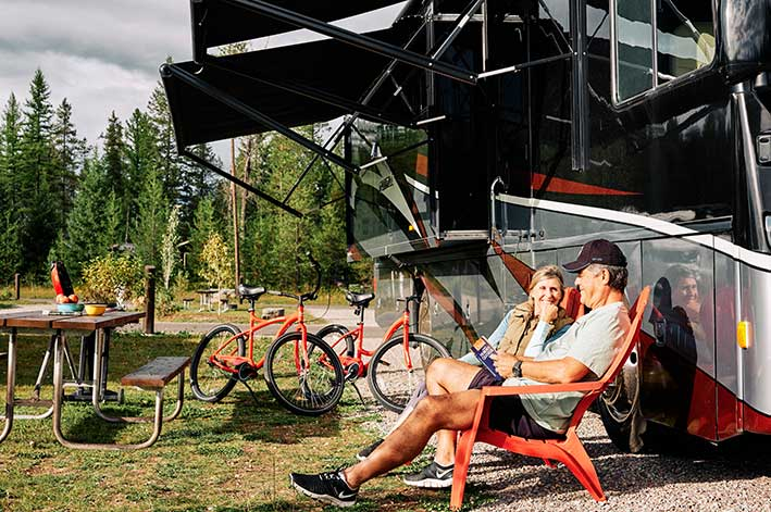 A couple sits in adirondack chairs next to their RV