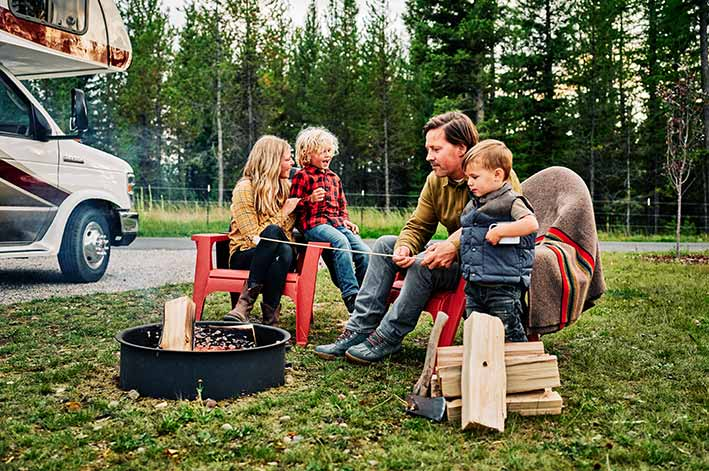 A couple with young children sit by a fire pit roasting marshmallows