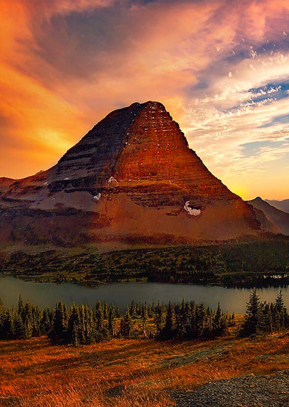 Golden sunlight shines on Bearhat Mountain and a lake below