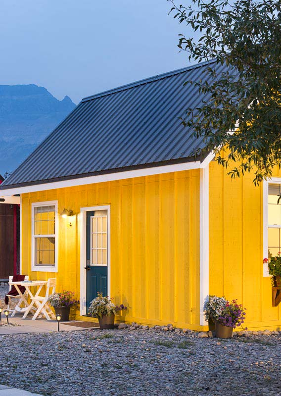 A yellow Tiny Home glows in the dusky hours of the day with planters of flowers all around