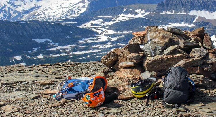 Safety gear resting on the ground with a mountain backdrop