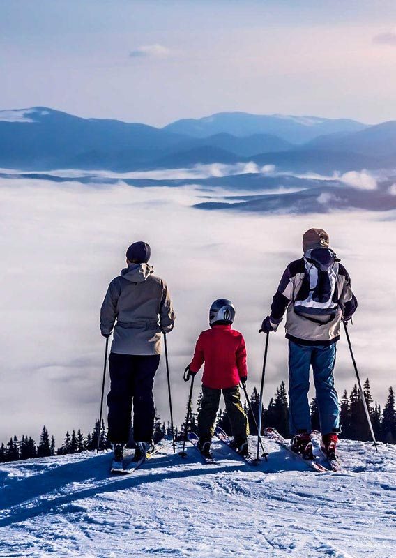 Family on the top of the mountains on skis
