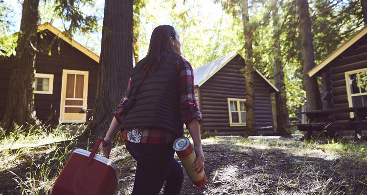 A woman carrying a thermos and cooler walks towards cabins set among trees