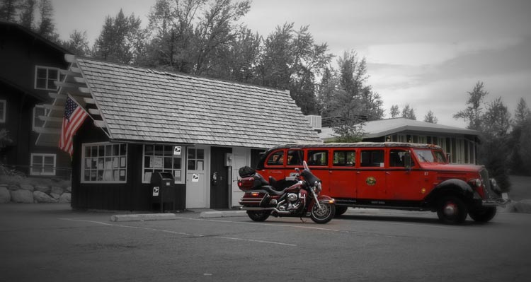 A red bus sits in front of a small wooden building