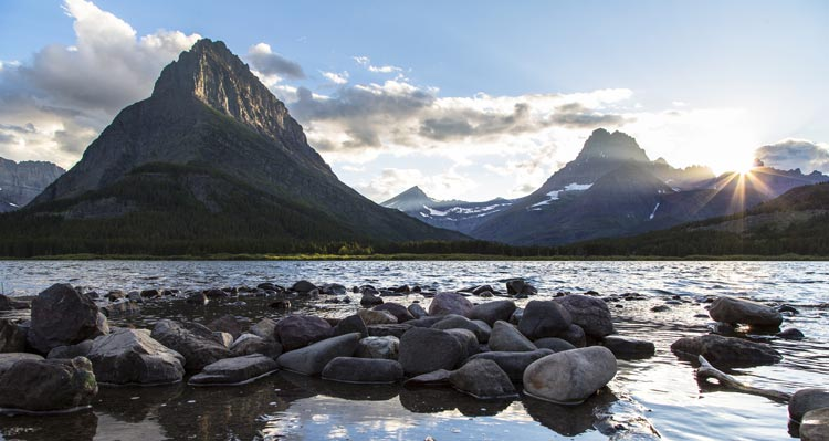 A view of mountains at sunset across Swiftcurrent Lake